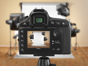 Digital photo camera in studio with softbox and flashes.